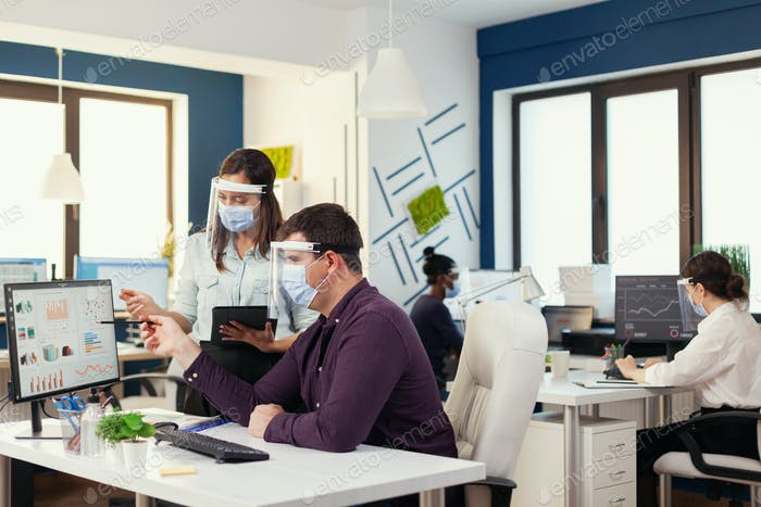international team doing financial analysis wearing face mask as safety precaution