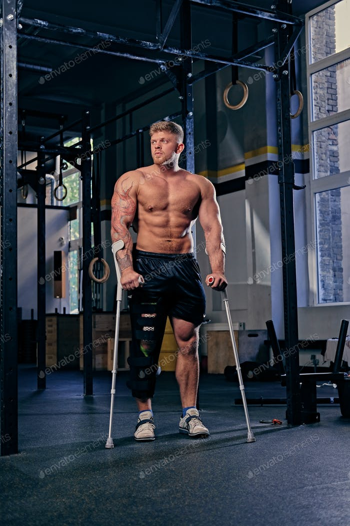 Shirtless bodybuilder on crutches near cross fit stand.