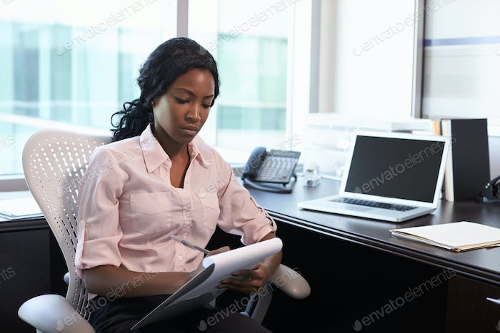 Female Doctor Sitting At Desk In Office Making Notes
