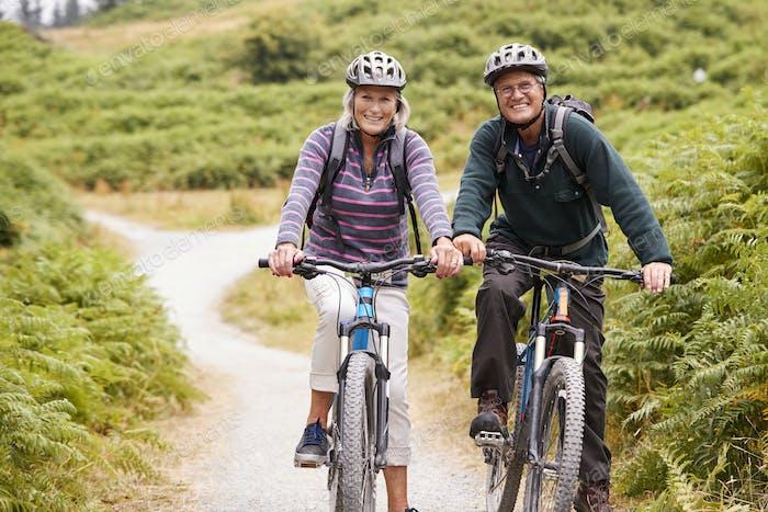 Senior couple sitting on mountain bikes in a country lane