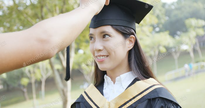 Father help her daughter adjust the mortarboard in graduation day