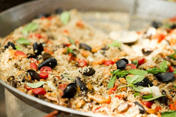 Close up of pilaf with mussels in big bowl for sale on city picnic