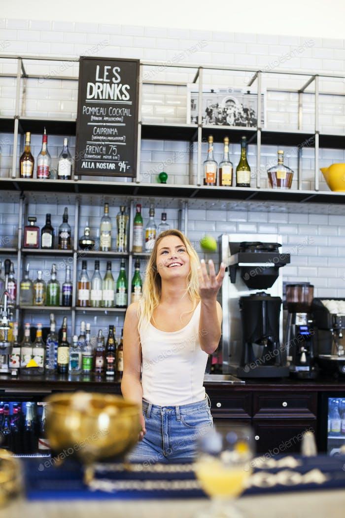 Glückliche Frau jongliert an der Theke im Café