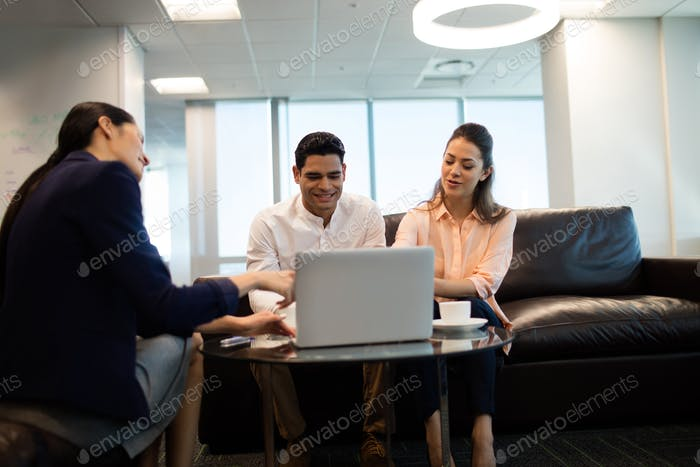 Business people discussing over laptop at office