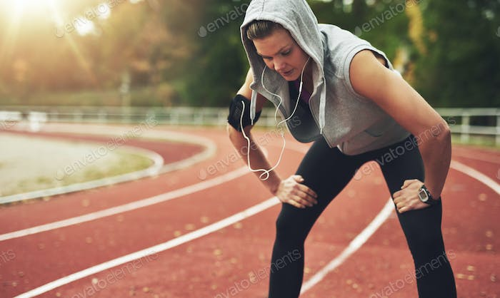 Fit young woman standing on track field and listening to music