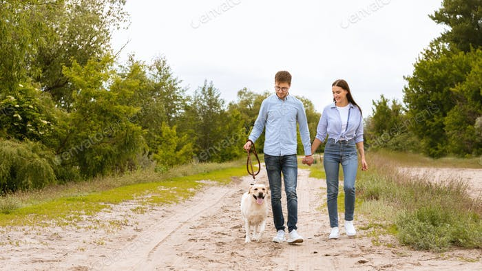 Excited couple and golden retriever walking in countryside