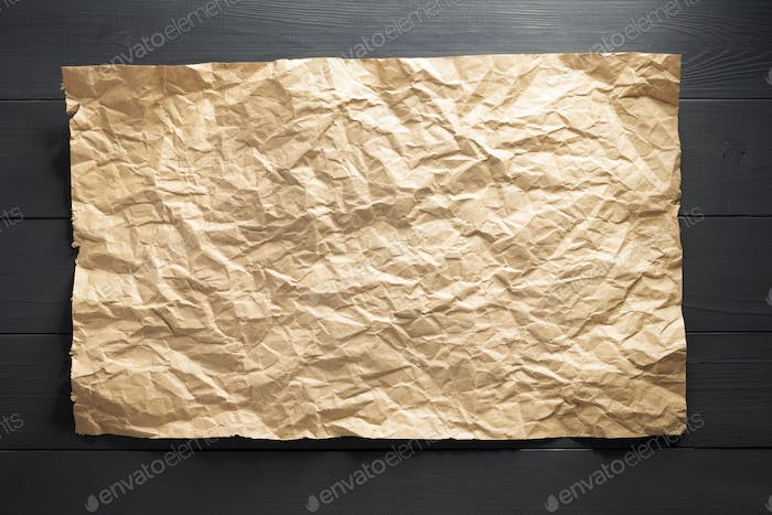 wrinkled paper at wood