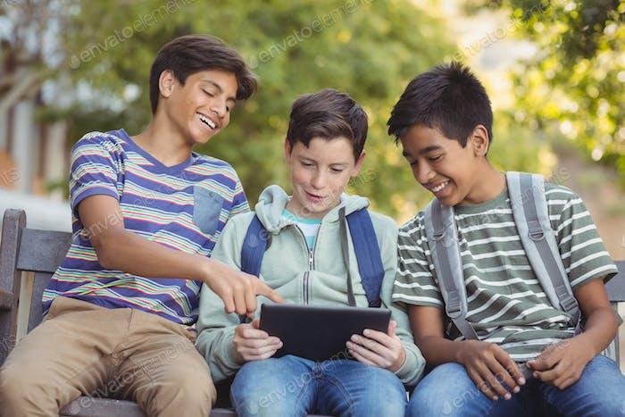 School kids using digital tablet on bench