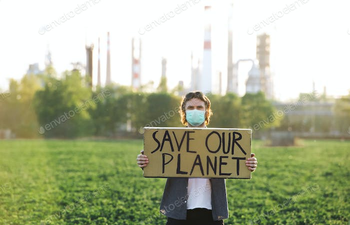 Young activist with placard standing outdoors by oil refinery, protesting