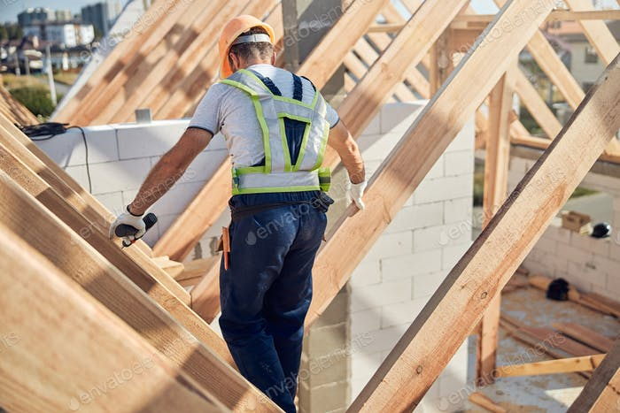 Cautious contractor working on a roof of a constructed building