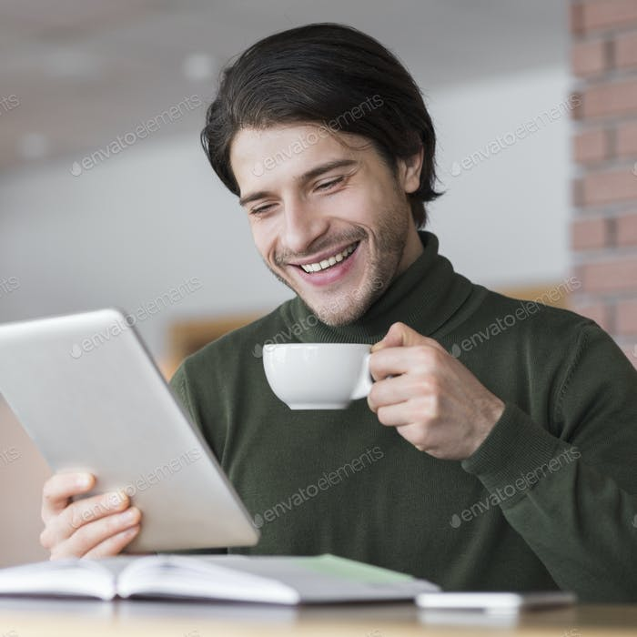 Young successful businessman checking emails while having morning coffee