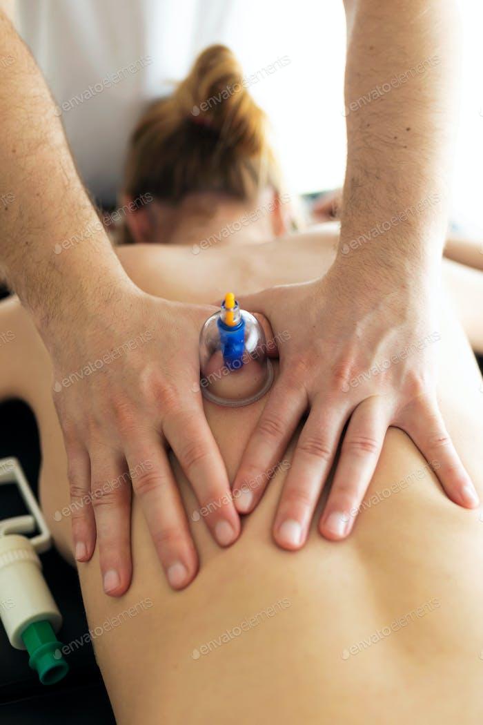 Physiotherapeut wendet Schröpfbehandlung an den Patienten in einem Physiotherapieraum an.