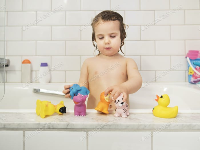 Girl playing with rubber toys in bathtub