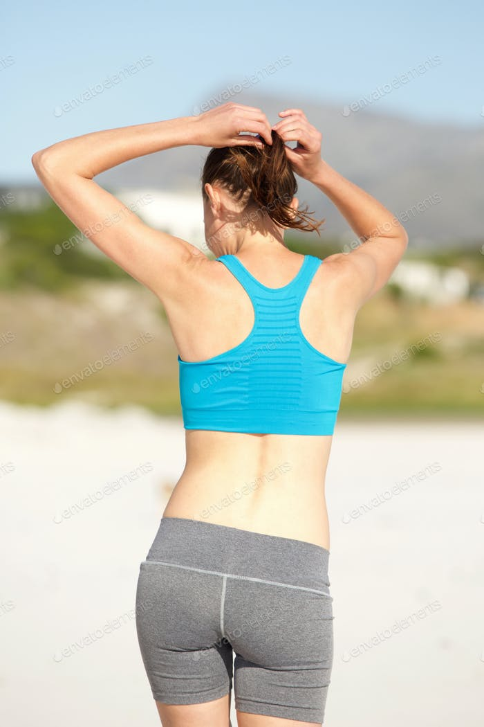 Woman getting ready for workout at the beach