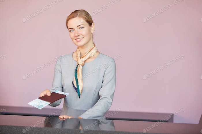 Young Woman Working at Check In Desk in Airport