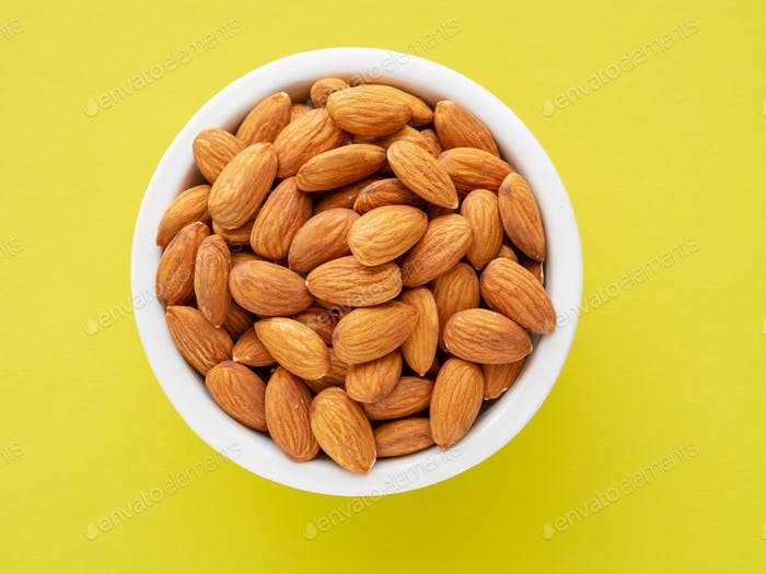 Top view of white cups, bowls with a handful of pecans, almonds on a bright yellow background color