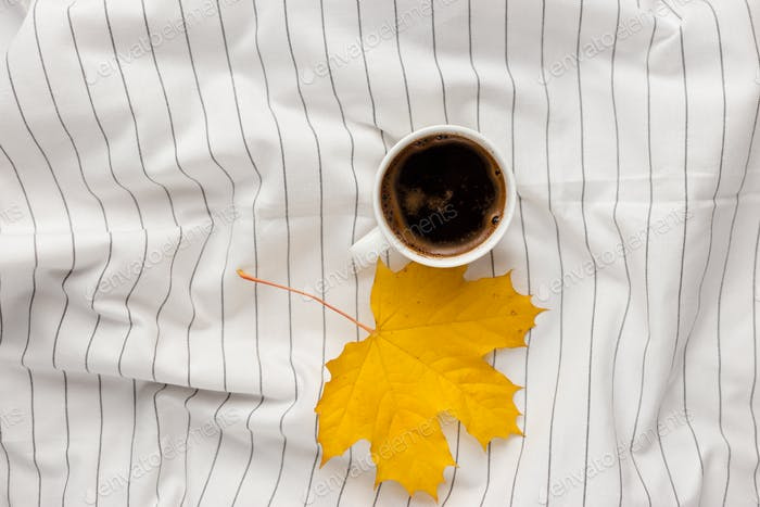 Autumn composition. Cup of coffeecup, autumn leaves on on white checkered cloth