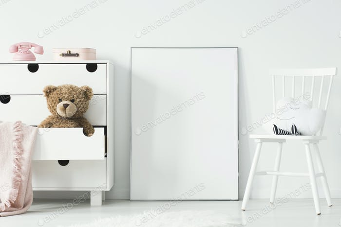 Mockup of white empty poster between chair and cabinet in child'
