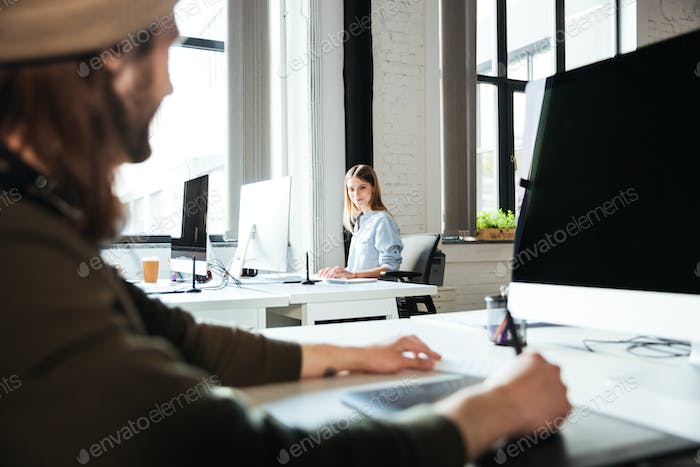 Young colleagues work in office using computers