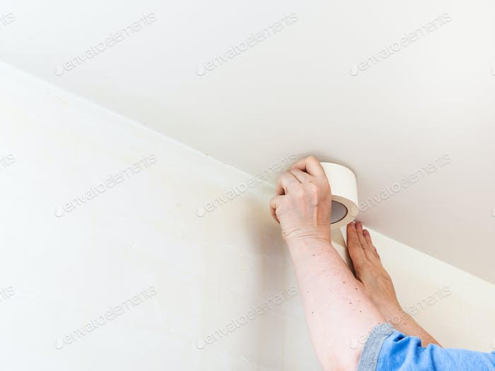 Decorator fixes tape on wall before painting
