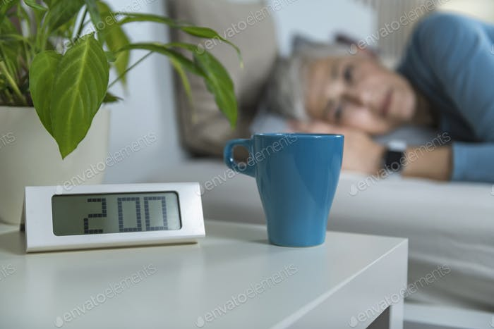 Digital Alarm Clock at Night Table. Sleepless Female in Background Suffering From Insomnia