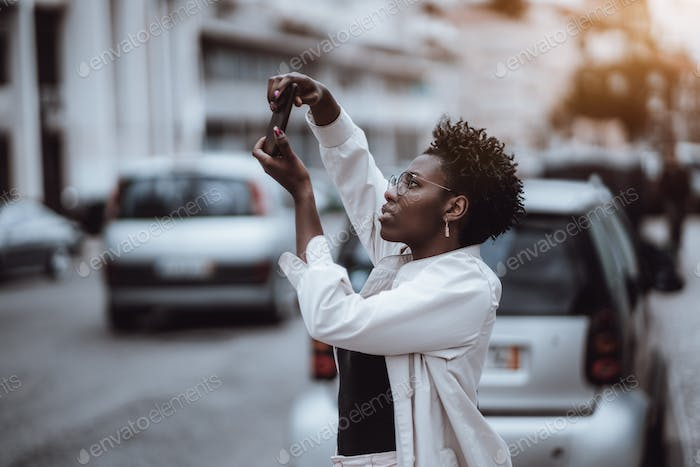 Black girl is taking pics outdoors