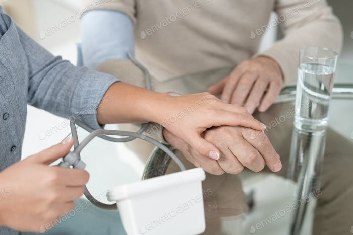 Hands of young woman with tonometer measuring blood pressure of her sick father