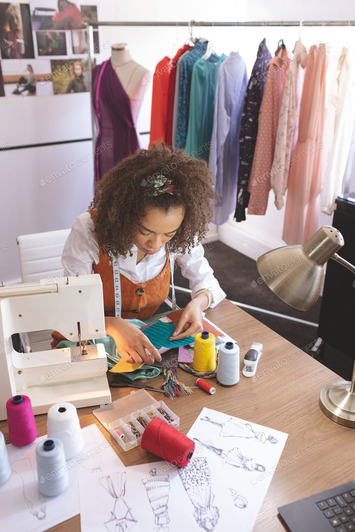 High angle view of young Mixed-race female fashion designer working in design studio