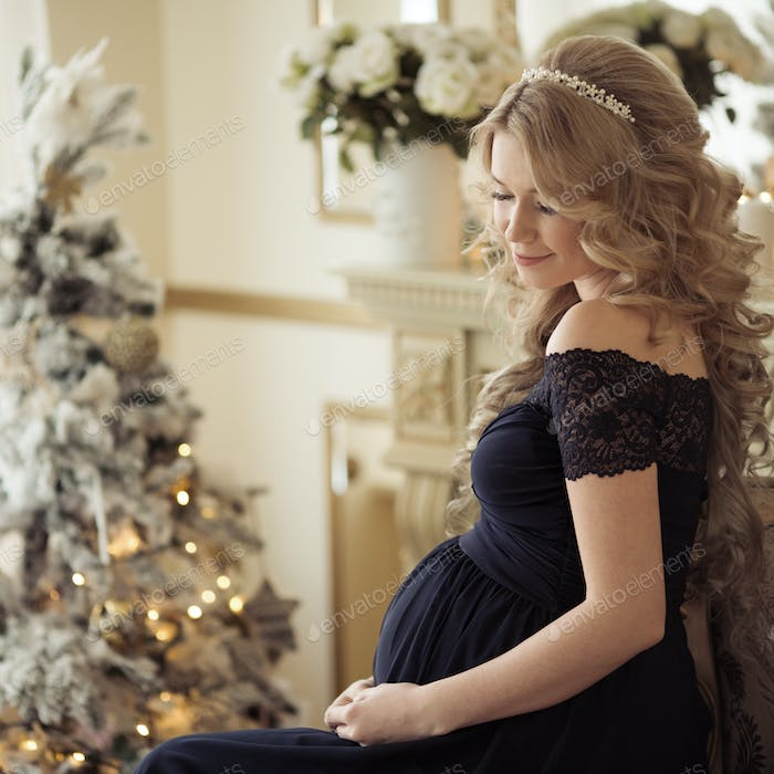 Beautiful Pregnant Woman In A Holiday Dress. Christmas Tree Back
