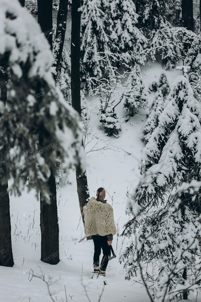 Wikinger Krieger mit Mohawk Haarschnitt und Wolf Fell Rüstung hält Axt