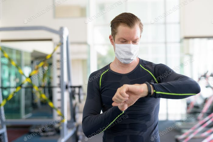 Young man with mask for protection from corona virus outbreak checking smartwatch at gym during