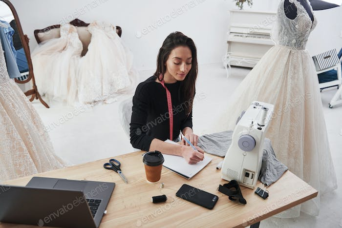 Female fashion designer works on the new clothes in the workshop