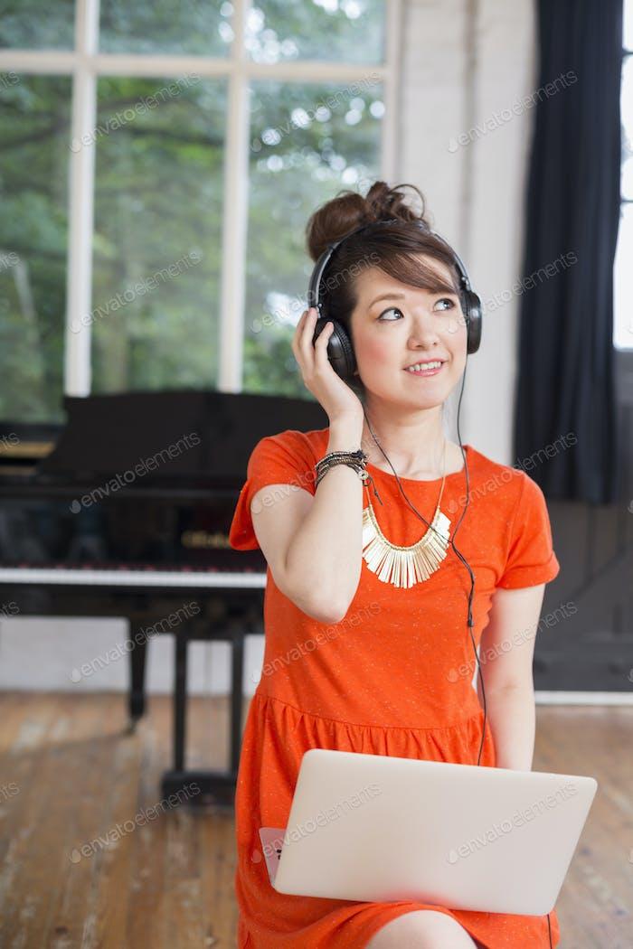 Молодая женщина в наушниках с ноутбуком