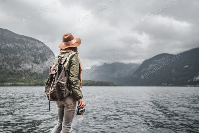 Young photographer in a hat by the lake