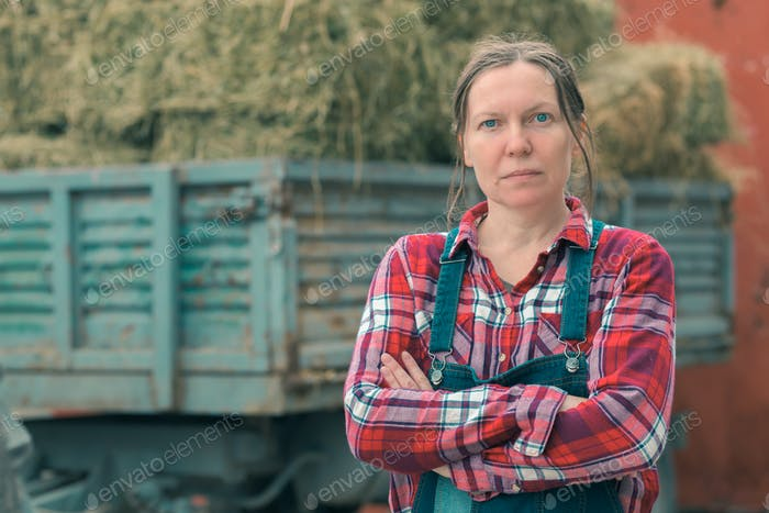 Female farmer posing in front of hay wagon