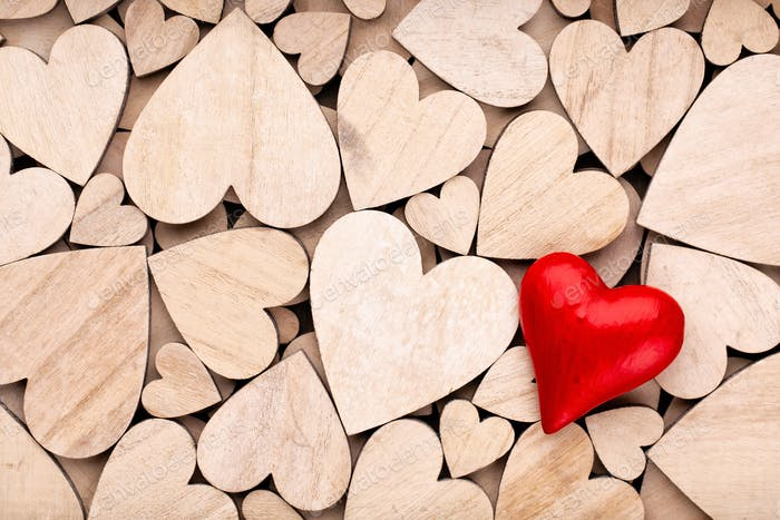 Wooden hearts, one red heart on the wooden heart background.