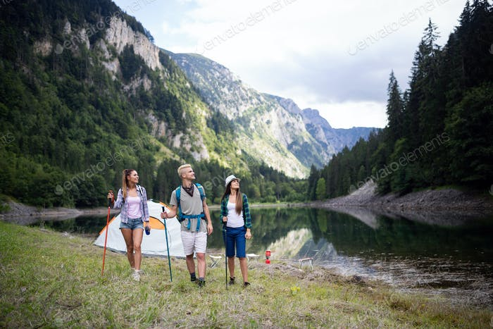 Group of young friends hiking in countryside. Multiracial happy people travelling in nature