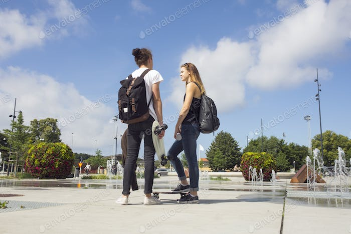 Teenage girl (14-15) and teenage boy (16-17) hanging out in skateboard park
