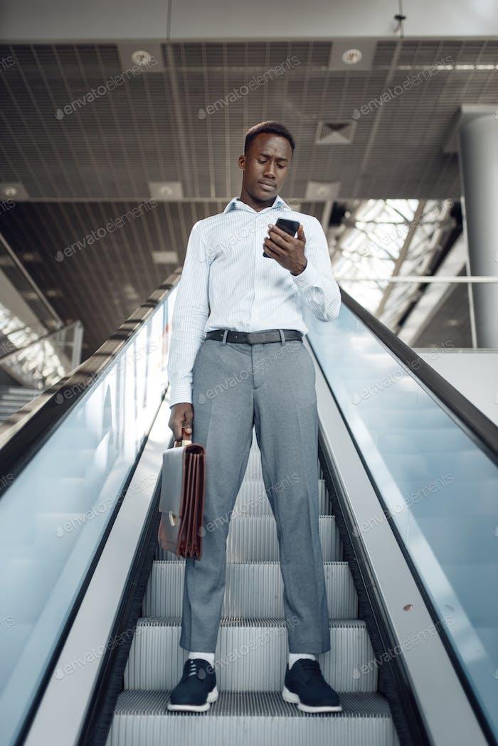 Businessman talking by phone on escalator in mall