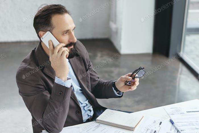 Thoughtful businessman thinks about offer of collaboration, talks on mobile phone with mobile phone,