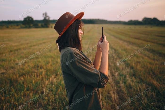 Hermosa mujer elegante en sombrero tomando foto de la puesta de sol en el teléfono en el campo de verano. Momento atmosférico