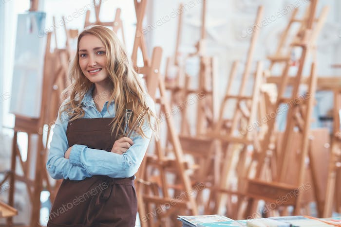 Young attractive woman on the background of easels