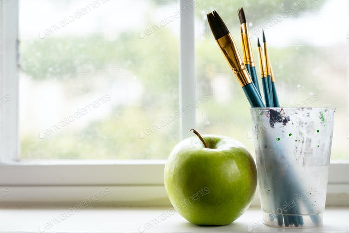 Paint brushes with a green apple next to window