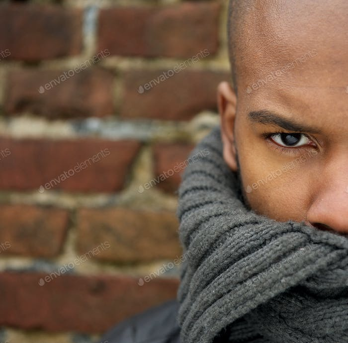 Attractive male fashion model with scarf covering face