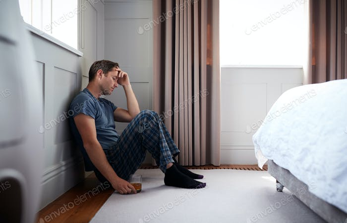 Depressed Man Wearing Pajamas Sitting On Floor Of Bedroom Holding Glass Of Whisky