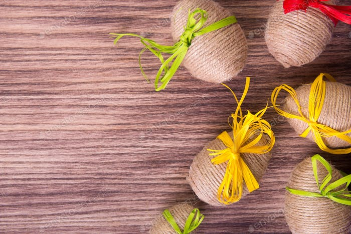 Easter egg in twine near wooden background.
