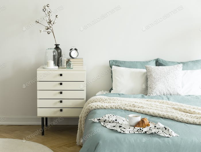 Coffee cup and croissant placed on double bed in real photo of w