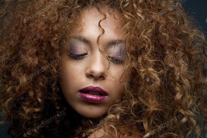 Beauty portrait of a female fashion model with curly hair and ma