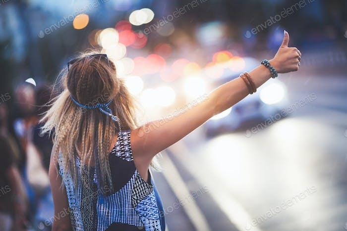 Woman hailing a cab at night while raining