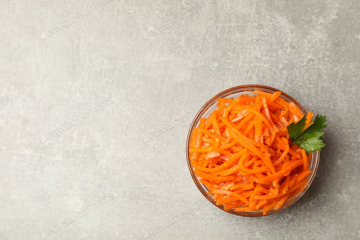 Tasty carrot salad on gray background, top view